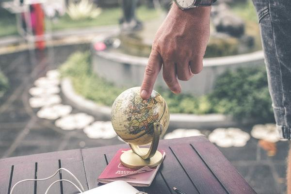 person pointing to a terrestrial globe