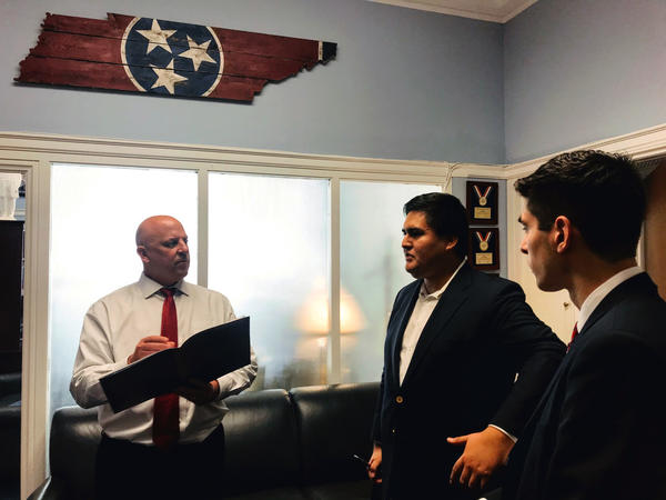 DesJarlais writes in a notebook as he listens to Macuri-Espinoza talk. Above his head are wooden planks cut into the shape of Tennessee with the state's flag--three white stars on a blue circle surrounded in red--painted on them.
