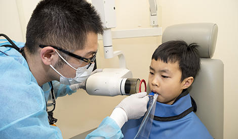 child having teeth xrayed by dentist