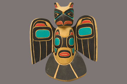 Carved cultural artifact with black, turquoise, and red colors.