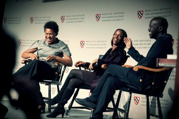 Three people laughing, seated in a panel leading discussions
