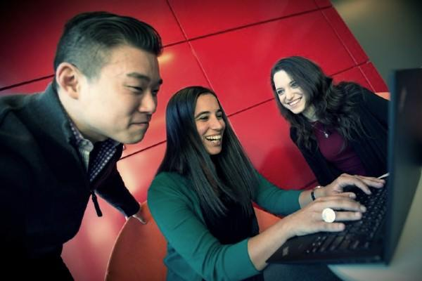 Three people looking into a computer screen. Behind them is a tile wall