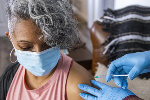 A person with brown skin and gray hair receiving a shot in the arm by another person wearing blue gloves.
