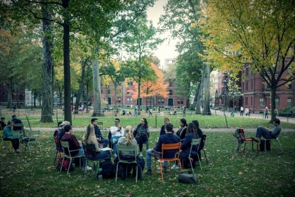 People sitting in chairs in Harvard Yard meeting together in a circle