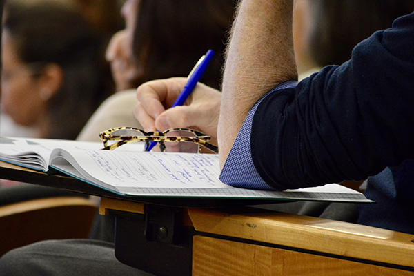 image of person taking notes with glasses on their notebook