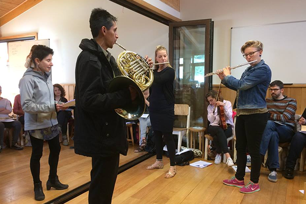 students playing a french horn and a flute