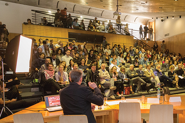a lecture hall filled with people listening to a speaker