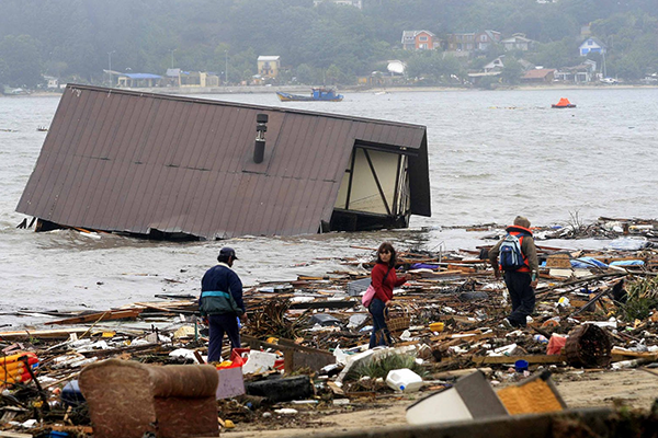 disaster striken scene in Chile, a house underwater and people walking through rubble