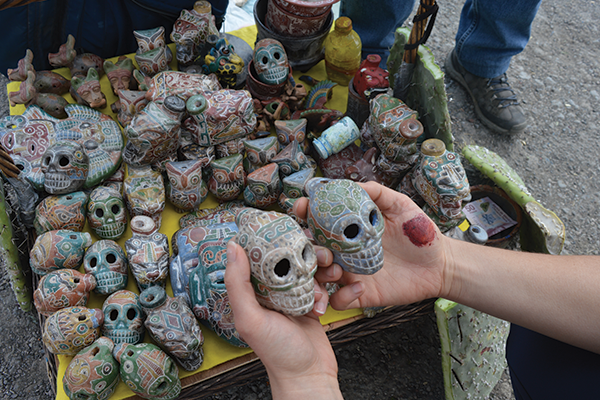 hands holding sugar skulls in Mexico (photo by Dani Perez)