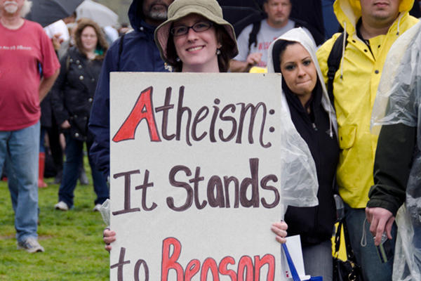 Woman with sign that says Atheism: it stands to reason
