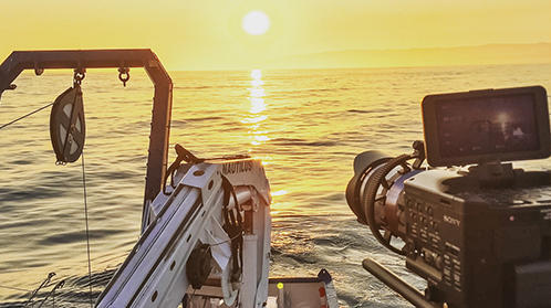 Image of camera recording ship at sunset