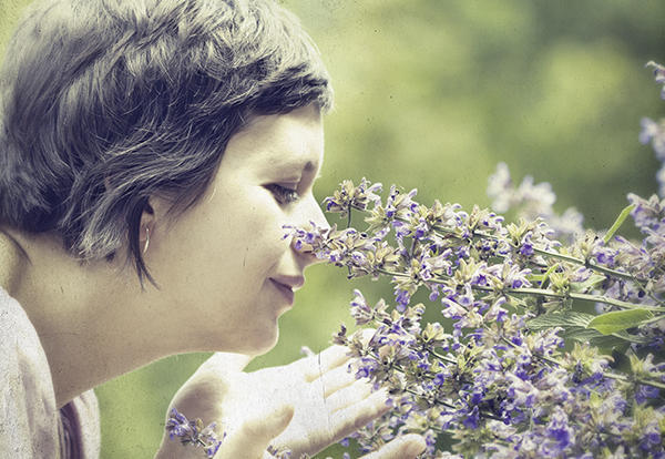 Woman smelling a plant.
