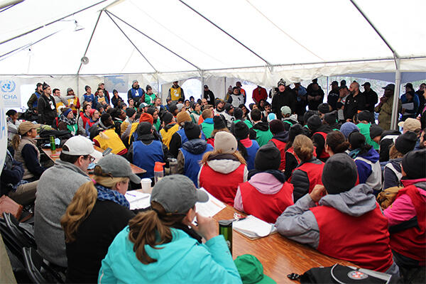 crowded meeting with lots of people in a tent