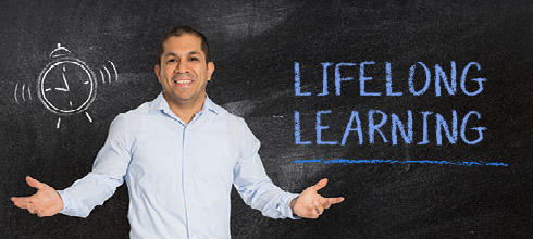 Man in front of chalkboard - Andy Lifelong Learning
