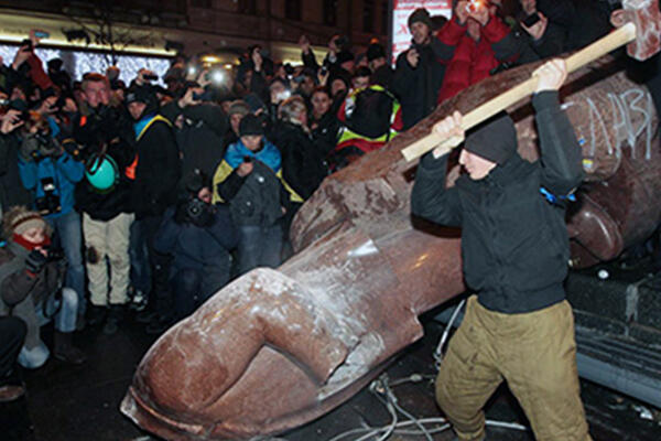 man with sledgehammer with crowd next to fallen statue
