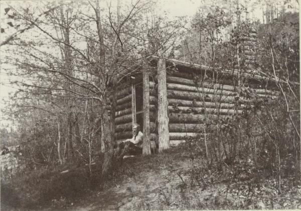 Image of Brewster sitting on front step of his small cabin in Concord, Mass.