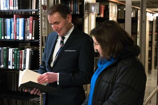 President Johannesson enjoys flipping through a book in the Widener stacks