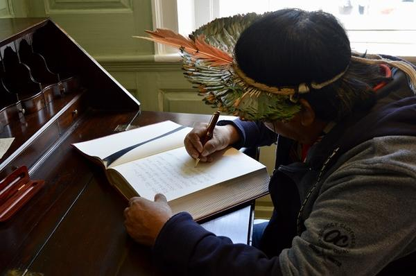 Davi Kopenawa signs the university guest book at Wadsworth House