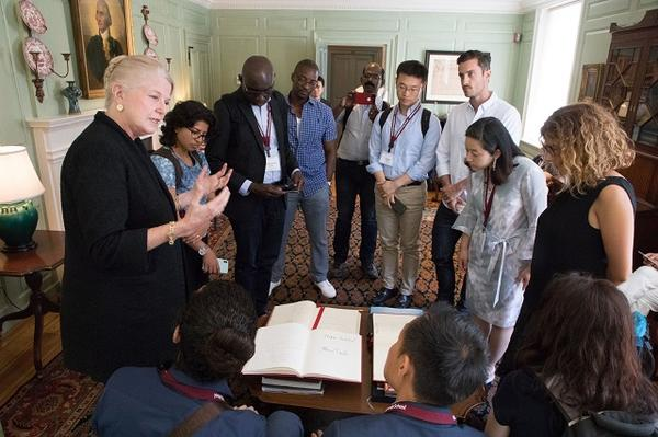 Margot Gill explaining the university guest book to the Mason Fellows