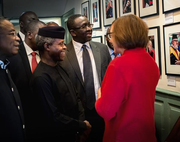 The University Marshal shows the Vice President of Nigeria the Harvard Commencement photo gallery in Wadsworth House