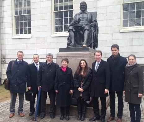 Members of the Swiss Parliament pose with their Crimson Key tour guide at the John Harvard statue.