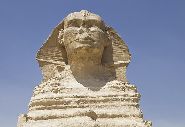 A mythical creature, the sphinx which has a body of a lion and the head of a human, lying down in the desert.