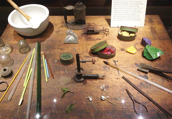 Work table with colored glass, mortar and pestle.