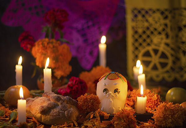 A decorated altar with colorful skull, candles and flowers in remembrance for loved ones who have passed away;