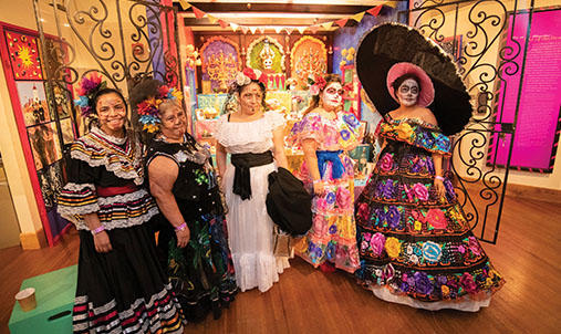 Five diverse women wearing dresses and some wearing makeup of a skull.