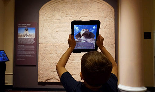 A boy holding an Ipad with a sphinx on the screen in front of a stele.