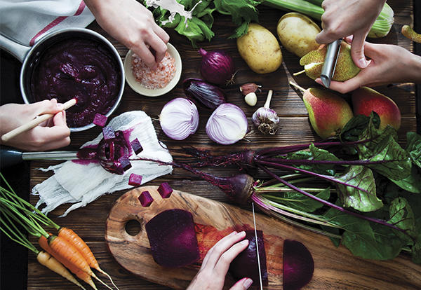 Variety of bright vegetables, such as carrots, onions, beets, being cut by three sets of hands.