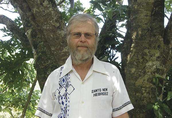 Bearded older man, speaker Matthew Spriggs, standing in front of a tree.