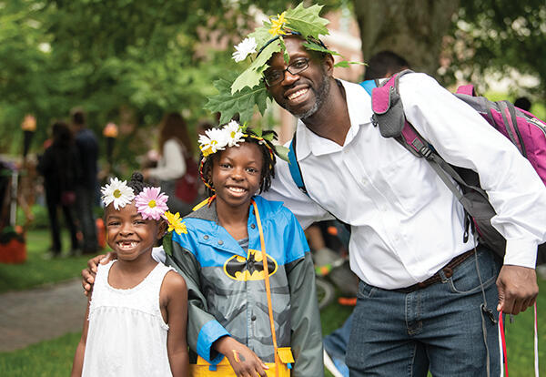 An older African American man with two African American children wearing flower crowns.