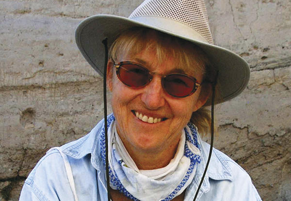 Woman, speaker Mary C. Stiner, smiling for a camera outside with a large rimmed hat and sunglasses on.