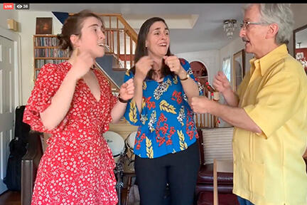 Two women and a man singing in their home.