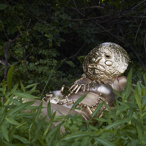 figure reclining in grass wearing a large, round, metallic mask