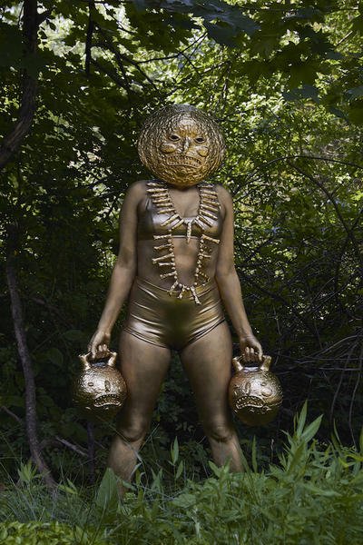 Human figure dressed in skintight metallic shorts, bra, and body paint, standing in lush green nature setting, wearing a large, round metallic mask, holding two metallic kettlebell-shaped vessels with faces on them.