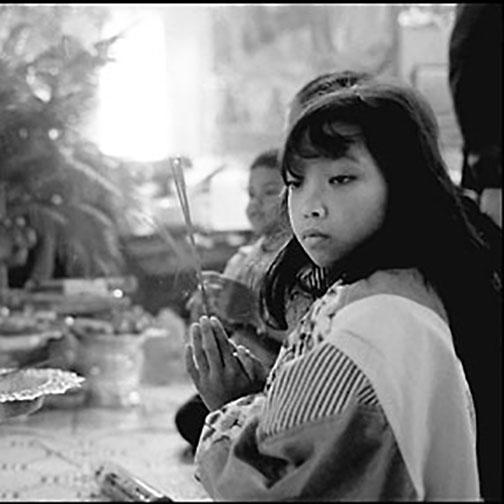 Child with incense at Buddhism temple