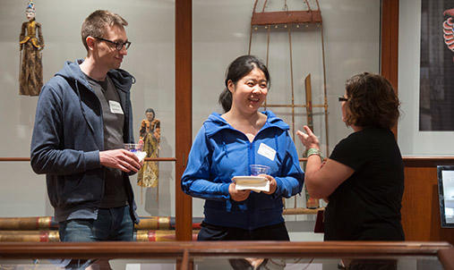 Three diverse people talking in a gallery at an event.