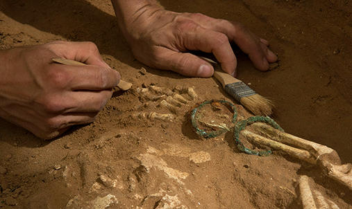 Close up of a person excavating an archaeological site