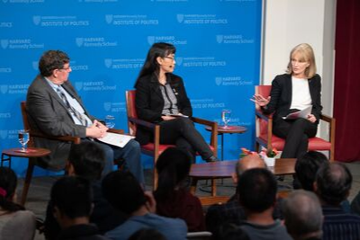 Three speakers sit engaged in discussion on a stage with a blue backdrop featuring the Harvard Kennedy School logo