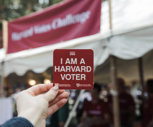 "Woman holds a card that reads ""I am a Harvard voter"""