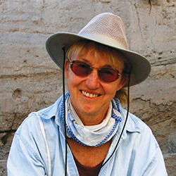 Woman, Mary C. Stiner, wearing a safari hat smiling at the camera.