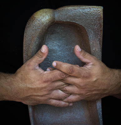 photo of hands clasped around a ceramic sculptural object by Seth Rainville