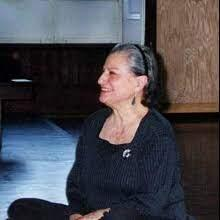 a candid photo of Claire Mallardi sitting in the studio. She is looking off camera in profile and smiling. Her hair is gray.
