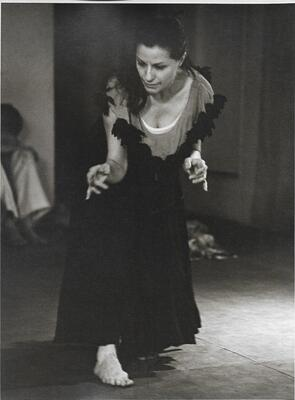 A black and white performance photo of Claire Mallardi. Her full body is in view and she is in mid-movement, her upper body poised over her bare foot that is peaking out from underneath her long flowing dress with fringe around the shoulders.