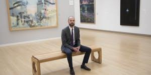 Photograph of man sitting on bench in museum