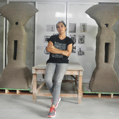 Ashwini Bhat standing in front of her large ceramic sculptures.