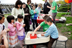 Children, adults and Harvard students participate in Ceramics wheel throwing at ARTS FIRST 2011