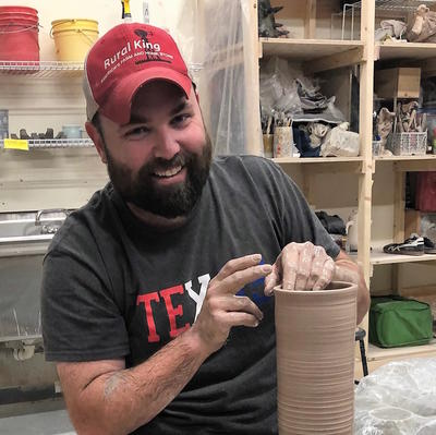 photo of bearded potter in red baseball cap wheel throwing a cylinder of clay
